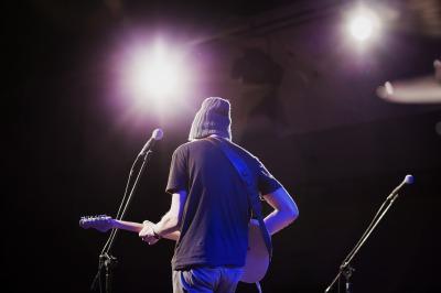 ギターを弾く後ろ姿の男性