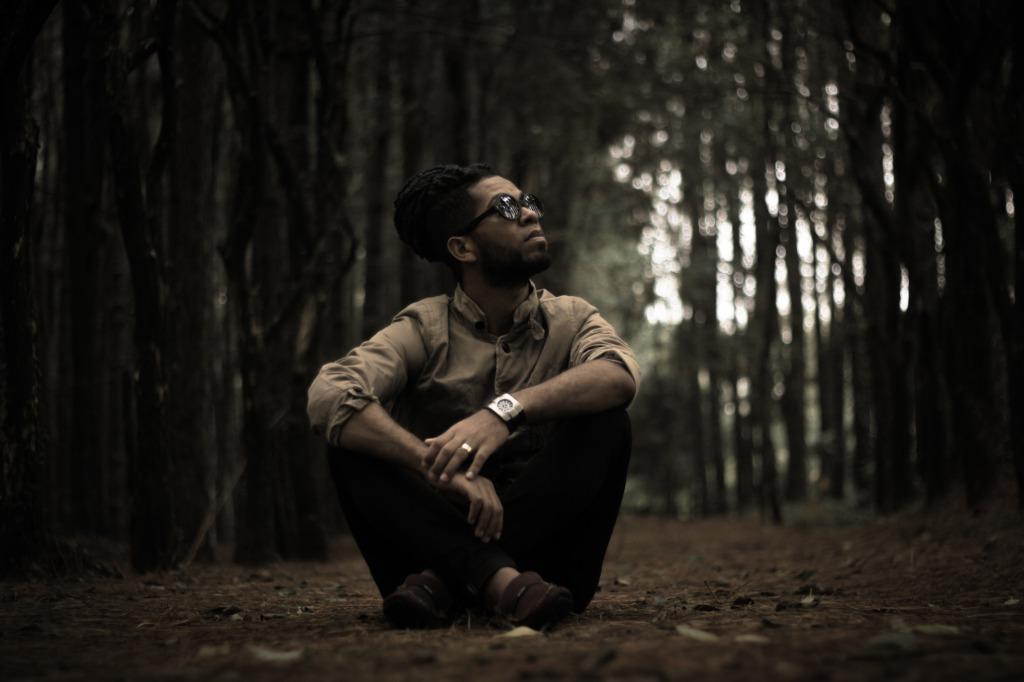 林の中に座り込む男性